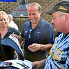 (Brad Davis/The Register-Herald) Former U.S. Marine Eva Pettry, left, and Alan Cummings, right, get some gear signed by football coach Dana Holgorsen on behalf of Newspapers In Education and the Women's Resource Center during the opening moments of the annual WVU Coaches Caravan Wednesday evening at Calacino's.