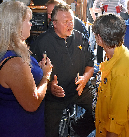 (Brad Davis/The Register-Herald) Men's basketball coach Bob Huggins chats with a couple of fans during the opening moments of the annual WVU Coaches Caravan Wednesday evening at Calacino's.
