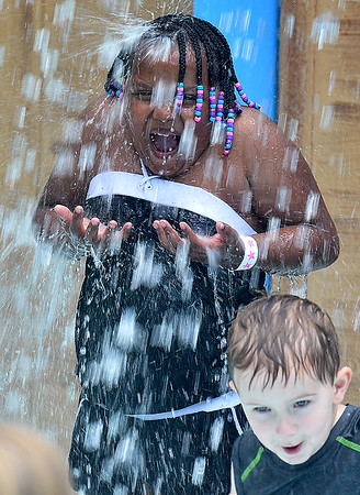 (Brad Davis/The Register-Herald) Seven-year-old Nymeria Jordan is doused by the bucket inside the Splash Park at Lake Stephens Saturday afternoon.
