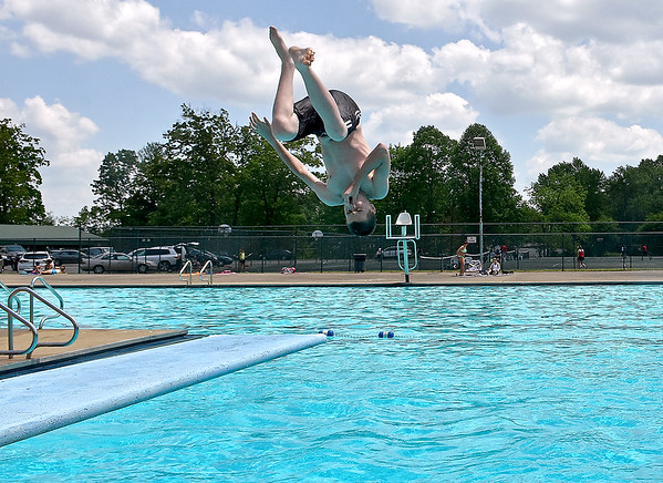 (Brad Davis/The Register-Herald) A young swimmer flips from one of the diving boards during opening day at the New River Park pool Saturday afternoon.