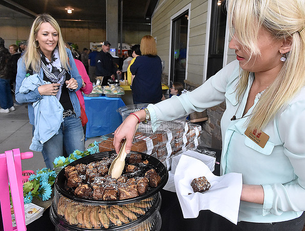 (Brad Davis/The Register-Herald) Beckley resident Rebecca Fadlevich, left, gets a couple of brownies from Bob Evans general manager Olivia Cox during Sweet Treats Dessert Festival Saturday afternoon inside the Intermodal Gateway.