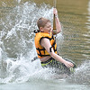 (Brad Davis/The Register-Herald) 10-year-old Charleston resident Blake Fallacker splashes down into the lake after a high speed run down the zip line during Ace Adventure Park's opening day Saturday morning in Minden.
