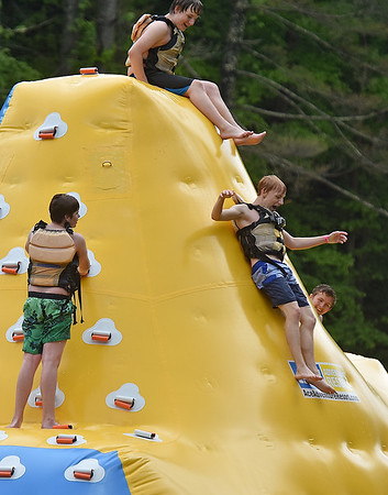 (Brad Davis/The Register-Herald) Swimmers climb on and jump from floating toys on the lake during Ace Adventure Park's opening day Saturday morning in Minden.