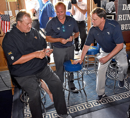 (Brad Davis/The Register-Herald) (From left) Men's basketball coach Bob Huggins, football coach Dana Holgorsen and women's basketball coach Mike Carey gather up some money for raffle tickets during the opening moments of the annual WVU Coaches Caravan Wednesday evening at Calacino's.
