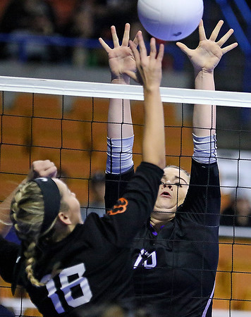(Brad Davis/The Register-Herald) James Monroe's Whitney Hunt leaps to block a hit from Chapmanville's Carley Cook during the Mavericks' opening round win in the class AA State Volleyball Tournament Friday morning at the Charleston Civic Center.