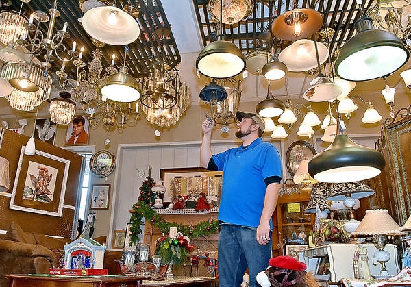 (Brad Davis/The Register-Herald) Mountaineer Electric Supply co-owner Justin Thornton double checks all the price tags on sale items inside their 612 South Eisenhower Drive location Friday morning in Beckley. Mountaineer Electric Supply is continuing its sale today for Small Business Saturday, featuring 25% off everything in store and 50% off on cloud lighting fixtures like the ones in the photograph.