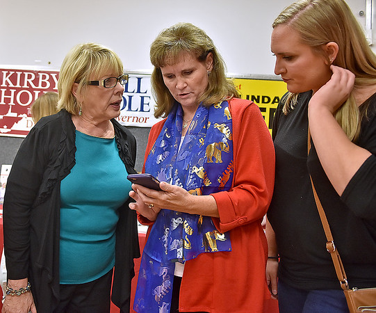 (Brad Davis/The Register-Herald) From left, Raleigh County Assessor candidate Linda Sumner, House of Delegates 35th district candidate Lynne Arvon and her daughter Kendra check results as they come in at Raleigh County GOP Headquarters Tuesday night.