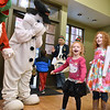 (Brad Davis/The Register-Herald) Two-year-old Zenna Zickafoose reacts after grabbing the carrot nose of Frosty the Snowman while her big sister Zia, right, looks on during the first ever Small Business Saturday shopping event yesterday in Uptown Beckley.