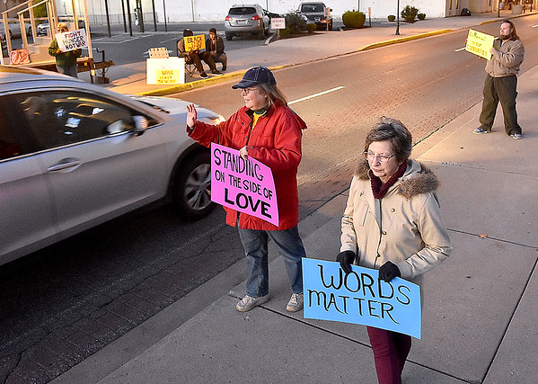 """(Brad Davis/The Register-Herald) Church members Cathy Abernathy, middle, April Puzzuoli, lower right, and a handful of other demonstrators wave at passing motorists as they """"Stand on the Side of Love"""" along Neville Street in front of Jim Word Memorial Park Thursday night. Stressing that it was not a protest, members of Beckley's New River Unitarian Universalist Fellowship, located at 911 South Kanawha Street, got out to encourage people to relax and have a little love for another following an intense election season."""