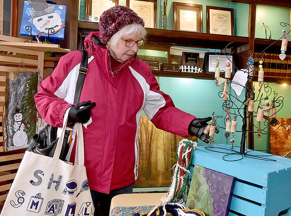 (Brad Davis/The Register-Herald) Beckley resident Meg Homan looks over items by artist Melanie Hicks during the first ever Small Business Saturday shopping event yesterday in Uptown Beckley.