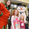 (Brad Davis/The Register-Herald) Two-year-old Zenna Zickafoose, lower right, and her sister Zia, 6, look on as they pose for photos with a Christmas elf and Frosty the Snowman during the first ever Small Business Saturday shopping event yesterday in Uptown Beckley.