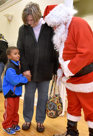 (Brad Davis/The Register-Herald) Four-year-old Sekou Sienta is a little shy as he's introduced to Santa Claus during the first ever Small Business Saturday shopping event yesterday in Uptown Beckley.