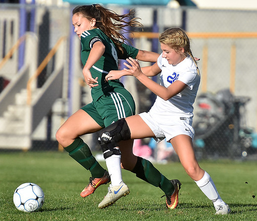 (Brad Davis/The Register-Herald) Fairmont Senior's Eviana Barnes battles for possession with Winfield's Syndey Cavender Friday evening at the YMCA Paul Cline Memorial Soccer Complex.