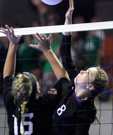 (Brad Davis/The Register-Herald) James Monroe's Jessica King hits the ball as Chapmanville's Carley Cook defends during the Mavericks' opening round win in the class AA State Volleyball Tournament Friday morning at the Charleston Civic Center.