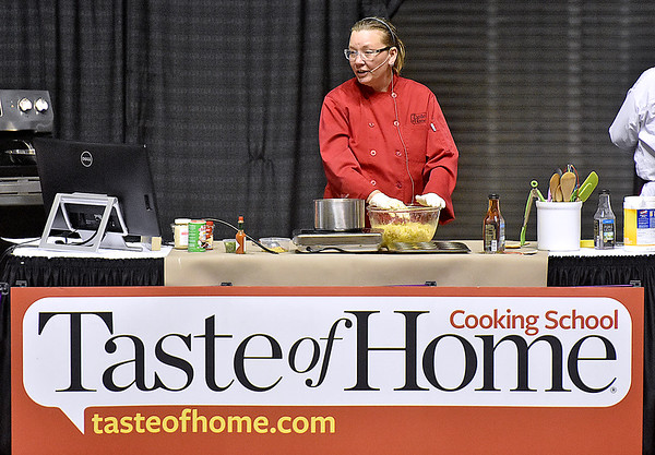 (Brad Davis/The Register-Herald) Culinary specialist Dana Elliott explains each step as she prepares a dish on stage during the annual Taste of Home Cooking School Thursday night at the Beckley-Raleigh County Convention Center.