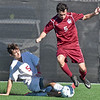 (Brad Davis/The Register-Herald) University's Nathanial Shuman tries to take the ball with a slide tackle on George Washington's Drew Goins during the Class AAA boys State Championship Saturday at the YMCA Paul Cline Memorial Sports Complex.