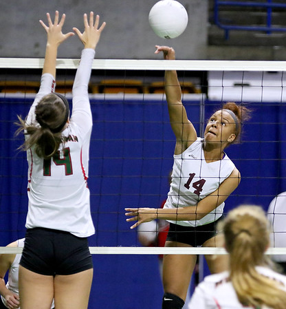 (Brad Davis/The Register-Herald) Woodrow Wilson's Makayla Walton hits the ball as Musselman's Sarah Wright defends during the Flying Eagles' second round loss to the Applemen in the class AAA State Volleyball Tournament Friday night at the Charleston Civic Center.