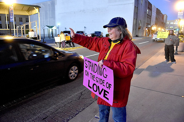 """(Brad Davis/The Register-Herald) Church member Cathy Abernathy and a handful of other demonstrators wave at passing motorists as they """"Stand on the Side of Love"""" along Neville Street in front of Jim Word Memorial Park Thursday night. Stressing that it was not a protest, members of Beckley's New River Unitarian Universalist Fellowship, located at 911 South Kanawha Street, got out to encourage people to relax and have a little love for another following an intense election season."""