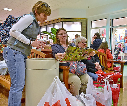 (Brad Davis/The Register-Herald) Beckley native and North Carolina resident Heather Campbell, left, looks over ads with friend Donna Flanagan (middle) to see if there are any more Black Friday deals to be had as they take a break from a day of shopping Friday evening inside the Crossroads Mall. Fellow friend Nancy Tuckwiller sits with them and looks on at right.