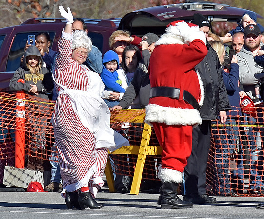 (Brad Davis/The Register-Herald) Santa Claus has to hold his hat as Mrs. Claus waves at the crowd through the blasting air of the helicopter as it takes off during his opening day arrival at the Crossroads Mall Saturday afternoon.