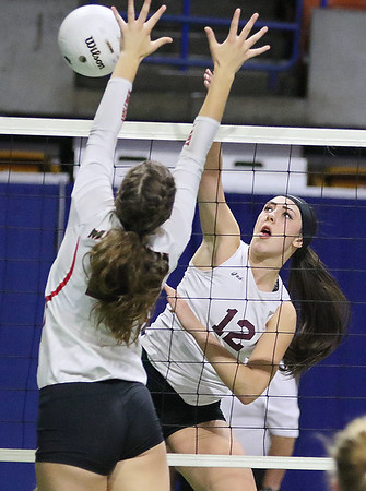 (Brad Davis/The Register-Herald) Woodrow Wilson's Makenzi Coulter hits the ball as Musselman's Haley Shelton defends during the Flying Eagles' second round loss to the Applemen in the class AAA State Volleyball Tournament Friday night at the Charleston Civic Center.