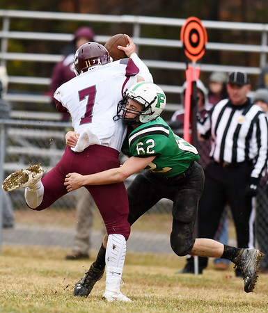 Fayetteville's Trent Pullens (62) sacks Wheeling Central quarterback (7) during the second quarter of their Class A quarterfinal game Saturday in Fayetteville. (Chris Jackson/The Register-Herald)