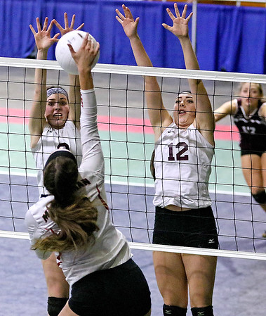 (Brad Davis/The Register-Herald) Woodrow Wilson's Sydney McClung, left, and Makenzi Coulter leap to try and block a hit from Musselman's Haley Shelton during the Flying Eagles' second round loss to the Applemen in the class AAA State Volleyball Tournament Friday night at the Charleston Civic Center.