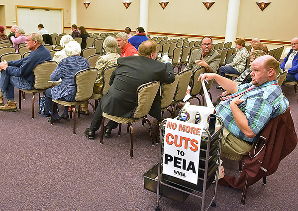(Brad Davis/The Register-Herald) John Quesenberry, far right, waits with other attending state employees for the start of Thursday night's public hearing on PEIA insurance rates at Tamarack.