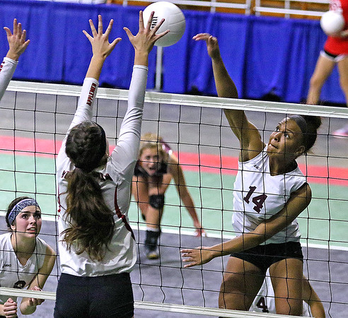 (Brad Davis/The Register-Herald) Woodrow Wilson's Makayla Walton hits the ball as Musselman's Haley Shelton defends during the Flying Eagles' second round loss to the Applemen in the class AAA State Volleyball Tournament Friday night at the Charleston Civic Center.