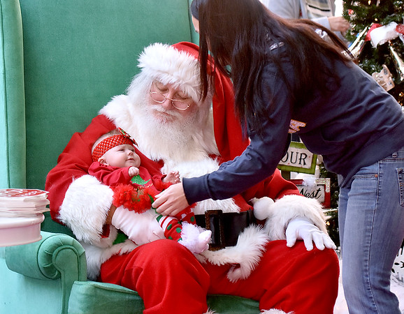 (Brad Davis/The Register-Herald) Beckley resident Mary Sizemore gently places her four-month-old daughter Payton Snuffer in Santa's arms as one of the first little ones to meet him on his opening day arrival at the Crossroads Mall Saturday afternoon.