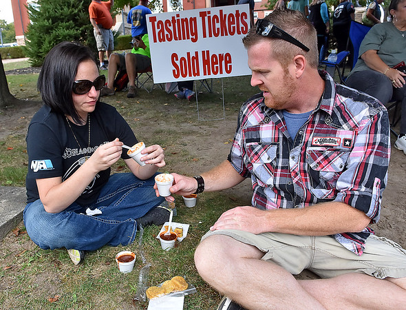 (Brad Davis/The Register-Herald) Joanna Walley and Alan Akers sample several different chili offerings during the Fayetteville Chili Cook-Off Saturday afternoon on Court Street.