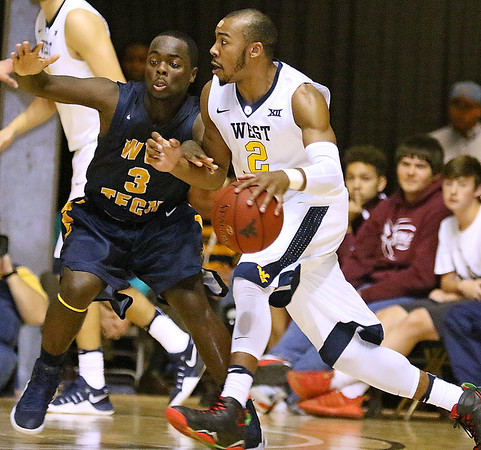 (Brad Davis/The Register-Herald) WVU's Jevon Carter drives along the perimeter as WVU Tech's Junior Arrey defends during the Mountaineers' exhibition game with the Golden Bears Saturday night at the Beckley-Raleigh County Convention Center.
