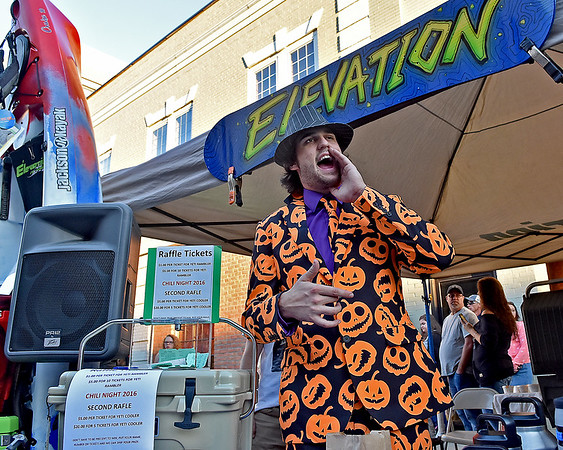 (Brad Davis/The Register-Herald) Dressed perfectly for the season, Elevation Sports' Ryan Ratcliff does his best street salesman impression as he tries to woo chili fans to their booth during Chili Night Saturday evening in uptown Beckley.