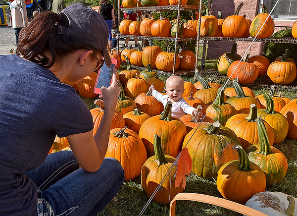 (Brad Davis/The Register-Herald) Oak Hill resident Taylor Morton, left, snaps away and films on her phone as her 9-month-old son Conner gets a kick out sitting in a field of pumpkins during the Burlington United Methodist Family Services' annual Pumpkin Festival Saturday afternoon.