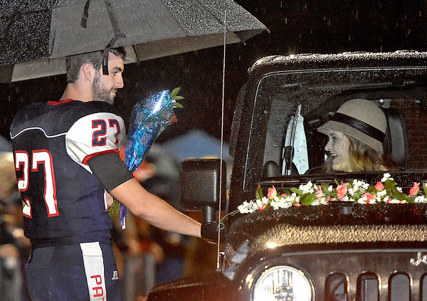 (Brad Davis/The Register-Herald) Indy senior Emily Ward, right in the jeep, is all smiles as she's greeted by her escort Logan Kelly, who holds an umbrella to keep them dry during homecoming ceremonies at halftime Friday night in Coal City.