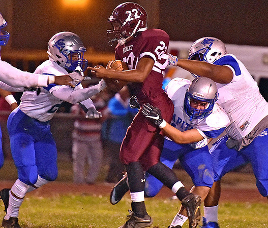(Brad Davis/The Register-Herald) Woodrow Wilson's Meeko Harris is taken down by a gang of Cougar defenders as he carries the ball during the Flying Eagles' game against Capital Friday night at Van Meter Stadium.