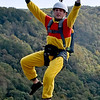 (Brad Davis/The Register-Herald) A BASE jumper gestures to the crowd on his way down from atop the New River Gorge bridge during the annual Bridge Day event Saturday afternoon.