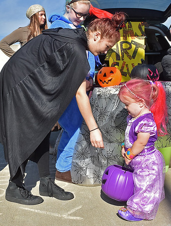 (Brad Davis/The Register-Herald) Independence Middle School Art Club student Kylie Stone, dressed as a dark heiress to a haunted estate, reaches down to give a piece of candy to four-year-old Kenzie Craddock, who is dressed up as a Shimmer & Shine character during Tailgate Halloween Saturday morning atop Beckley's Intermodal Gateway.
