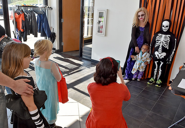 """(Brad Davis/The Register-Herald) At upper right, vampire Brianna Smith, 13, skeleton Preston Smith, 10, and """"old lady"""" Breileigh Smith pose while L &S Toyota employee Erin Stone smaps a photo for a halloween costume contest held by the dealership Saturday. From 9:00 a.m. to 5:00 p.m., anyone in a costume could stop by and enter with a quick photo by staff, then a winner was picked later in the day."""