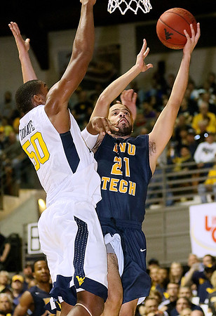(Brad Davis/The Register-Herald) WVU Tech's Enson Garcia drives to the basket as WVU's Sagaba  Konate defends during the Mountaineers' exhibition game with the Golden Bears Saturday night at the Beckley-Raleigh County Convention Center.