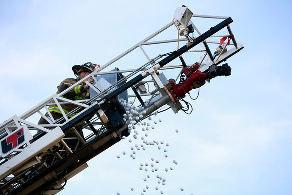 Sophia City Fire Department's Thomas Trent dumps 500 golf balls off of their ladder at Coal City Elementary School Friday in Coal City. The fundraising event was won by James May of Shady Spring.  (Chris Jackson/The Register-Herald)