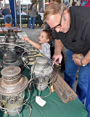 (Brad Davis/The Register-Herald) Three-year-old Jacob Southern is fascinated by an array of old train lanterns as his great grandfather Glen Ward looks over other historic railroad artifacts at the booth of retired signalman Bill Blackburn and his wife Tammy, who used to be a railroad dispatcher herself, during Railroad Days in Hinton Sunday afternoon.