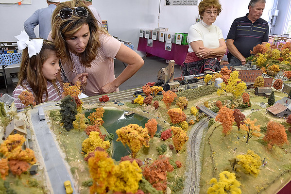 (Brad Davis/The Register-Herald) Nine-year-old Addisyn Sarver thinks she sees one of the tiny target items on her list of things to find as she and mother Kelli participate in the model train layout hunt inside the museum during Railroad Days in Hinton Sunday afternoon. Items to find inside the miniature railroad worlds would include things like kissing couples in city streets, cows in a farm field or a farmer in a corn field.