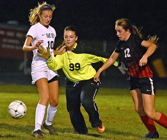 (Brad Davis/The Register-Herald) Oak Hill goalkeep #99 scrambles between teammate Jackie Rosiek and PikeView's Alexis O'Dell to get to a loose ball Wednesday night in Oak Hill.