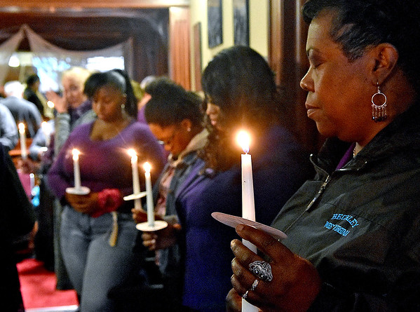 (Brad Davis/The Register-Herald) Attendees take a moment of silence to remember victims of domestic violence during the Women's Resource Center's 26th annual Candlelight Vigil and memorial service Saturday afternoon at The Raleigh Playhouse & Theatre.