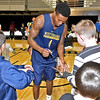(Brad Davis/The Register-Herald) WVU's Daxter Miles Jr. signs autographs for young fans on the court following the Mountaineers' practice Friday night at Beckley-Raleigh County Convention Center.