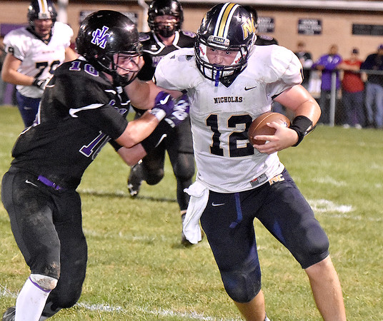 (Brad Davis/The Register-Herald) Nicholas County quarterback Tate Mays reaches up to stiff-arm James Monroe defender Connor Moore during the Grizzlies' road win over the Mavericks Friday night in Lindside.