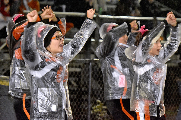 (Brad Davis/The Register-Herald) Summers County cheerleaders keep dry as they do their thing during the Bobcats' road game at Indy Friday night.