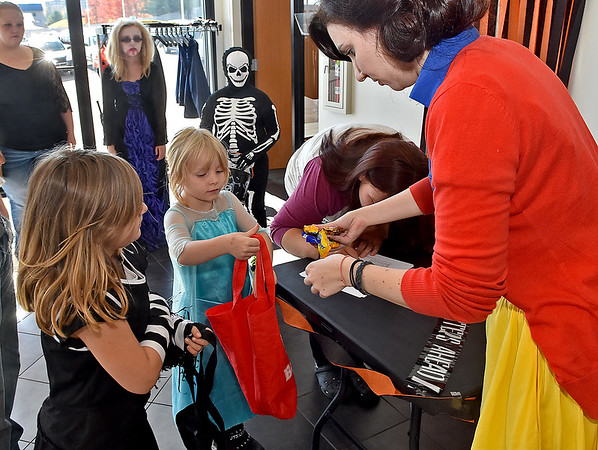 (Brad Davis/The Register-Herald) Costumed participants (from lower left) Isabella Templeton, 7, and Annabelle Browning get some candy from L & S Toyota employee Erin Stone, right, after getting their photos taken for a halloween costume contest held by the dealership Saturday. From 9:00 a.m. to 5:00 p.m., anyone in a costume could stop by and enter with a quick photo by staff, then a winner was picked later in the day. Vampire Brianna Smith, 13, and skeleton Preston Smith, 10, wait to get their photo taken in the background.