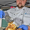 (Brad Davis/The Register-Herald) Executive Chef Eric Pierce prepares a portion of Greenbrier Valley Medical Center's braised pork cheek over smoked fontina grit cake during Taste of Our Town Saturday afternoon in Lewisburg.